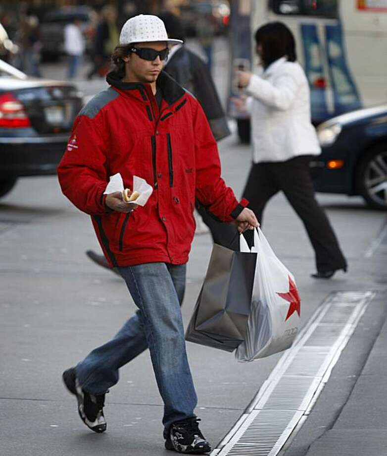 A Christmas shopper carries a hot dog and shopping bags across Geary Street to Union Square in San Francisco, Calif., on Tuesday, Dec. 1, 2009. Photo: Paul Chinn, The Chronicle