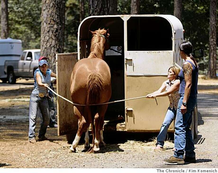 Sierra McCarthy, left, and her mother Casey McCarthy use a rope to move Rich Walls' horse into a trailer at the Paradise Horsemens' Association's horse evacuation center in Paradise, Calif., on Saturday, June 14, 2008. The center had more than 65 horses penned in existing paddocks as well as more than a dozen  makeshift stalls at the height of the Humboldt fire earlier this week.Photo by Kim Komenich / The Chronicle Photo: Kim Komenich, The Chronicle
