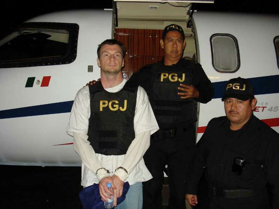 In this photo released by the Quintana Roo state Attorney General's Office on Thursday Feb. 9, 2012, reality television producer Bruce Beresford-Redman left, stands next to an airplane while in custody of police upon his arrival at the airport in Cancun, Mexico early Thursday, Feb. 9, 2012.  Photo: AP