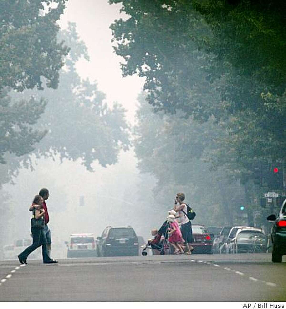 Smoke from nearby fires fills the air for those walking around in Downtown Chico Tuesday June 24, 2008. In less than a day, an electrical storm unleashed nearly 8,000 lightning strikes that set more than 800 wildfires across Northern California _ a rare example of