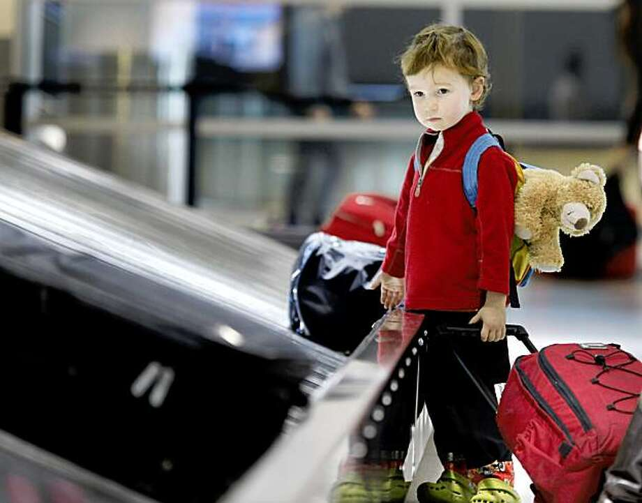 Sam Walker, 3, watched for the family luggage at the Southwest terminal.  He and his family are visiting from Seattle. Some people got an early start on their Thanksgiving holiday plans by arriving and departing from Oakland Airport Monday November 23, 2009. Photo: Brant Ward, The Chronicle