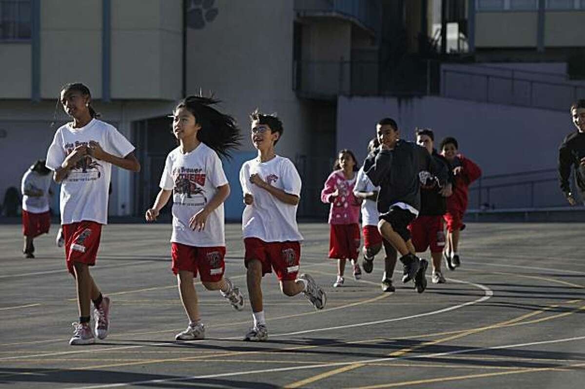 Angelic Vazquez, 11, Daqi Xuam, 12 and Nathaniel Trujillo, 11, lead a group of sixth graders at Edna Brewer Middle School during warmup laps in PE class on Monday Nov. 30, 2009 in Oakland, Calif. California's annual fitness gram results came out showing students are slightly more fit than last year.