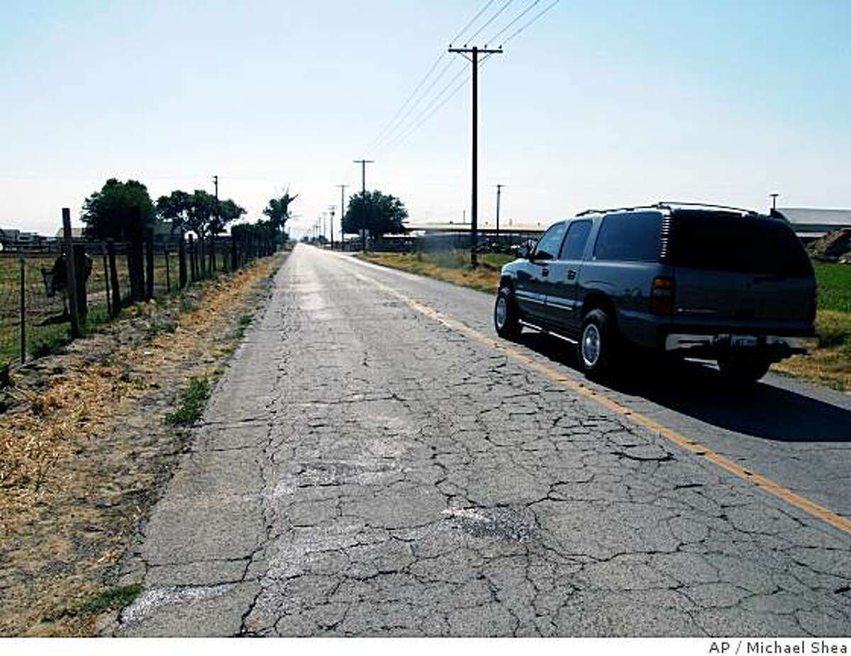 A vehicle travels past a blood stain on W. Bradberry Rd. east of Blaker Rd. in rural Stanislaus County, Calif. on Sunday, June 15, 2008. A Modesto Police Department officer flying in a police helicopter landed near a suspect that was beating a infant boy. The officer shot and killed the Turlock, Calif. man Saturday June 14th, 2008 as he attacked and killed the infant boy. (AP Photo/The Modesto Bee, Michael Shea)