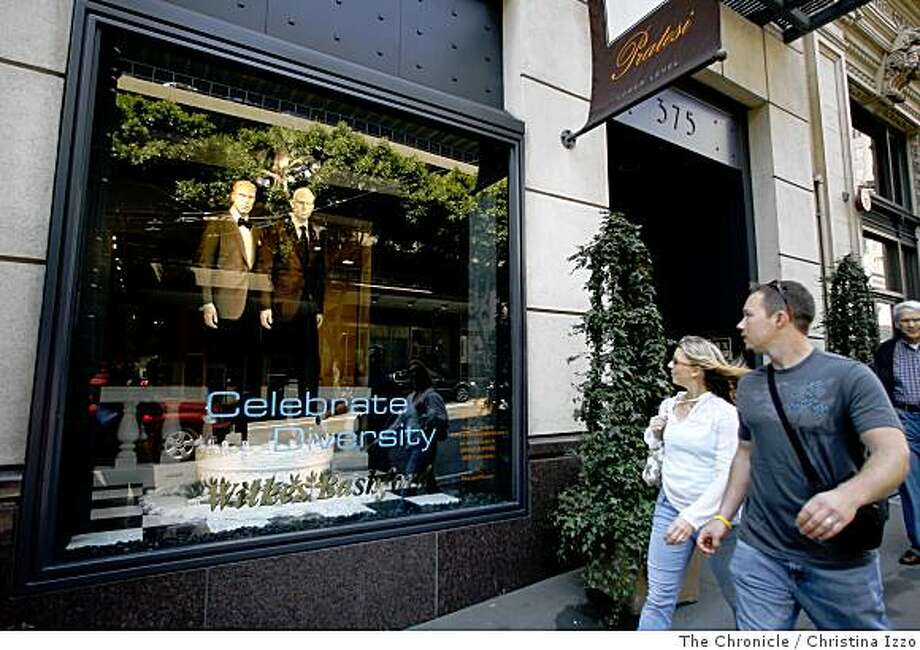 Passerbys observe a window display at Wilkes Bashford that shows same sex couples. Two window displays at Wilkes Bashford showcase very fashionably dressed, life like same sex couples on a giant wedding cake in San Francisco, Calif. Photo By Christina Izzo/ The Chronicle Photo: Christina Izzo, The Chronicle