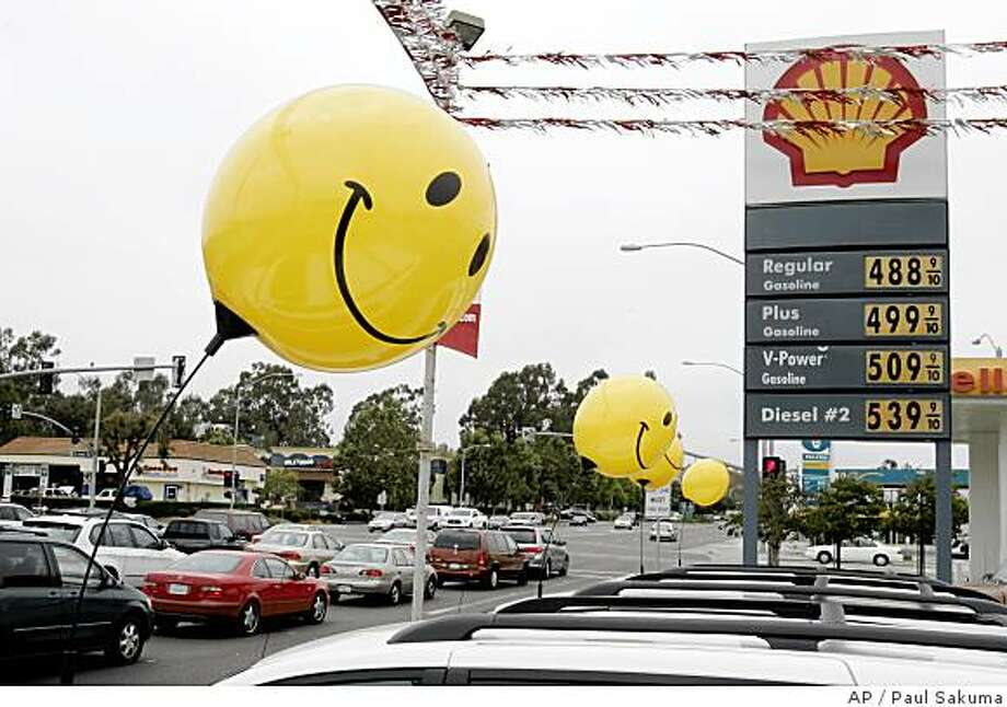 Balloons attached to cars at a car dealership sway in the wind near Shell station's price board in San Bruno, Calif., Monday, June 23, 2008. Oil prices rose Monday on disappointment over Saudi Arabia's modest production increase and concerns that output from Nigeria will decline. Retail gas prices, meanwhile, inched lower overnight, but appear unlikely to change much as long as oil prices stay in a trading range. (AP Photo/Paul Sakuma) Photo: Paul Sakuma, AP