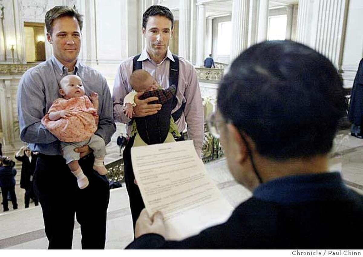 Eric Ethington (left) exchanges marriage vows with Doug Okun while holding their twin daughters, Sophia Rose and Elizabeth Ruby, in front of marriage commissioner Richard Ow at San Francisco City Hall.