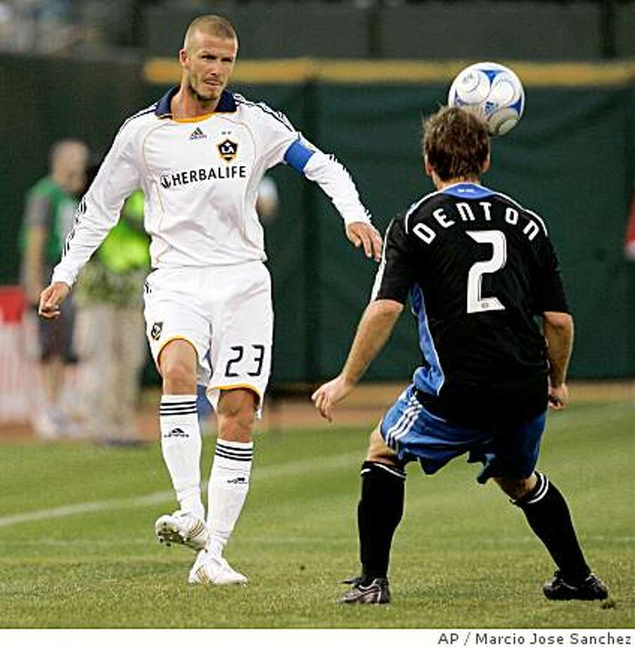 Los Angeles Galaxy's David Beckham, of England, chips the ball over San Jose Earthquakes' Eric Denton, right, in the first half of a soccer game in Oakland, Calif., Saturday, June 14, 2008. (AP Photo/Marcio Jose Sanchez) Photo: Marcio Jose Sanchez, AP