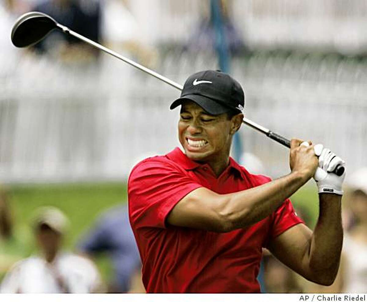 ** FILE ** In this June 15, 2008 file photo, Tiger Woods grimaces after teeing off on the second hole during the fourth round of the US Open championship at Torrey Pines Golf Course in San Diego. Woods will miss the rest of the season because of a left knee that will require more surgery, a person with knowledge of the decision said Wednesday June 18, 2008. (AP Photo/Charlie Riedel, File)