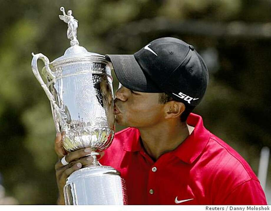 Tiger Woods kisses the U.S. Open trophy after winning a playoff round against Rocco Mediate at Torrey Pines in San Diego June 16, 2008. Photo: Danny Moloshok, Reuters