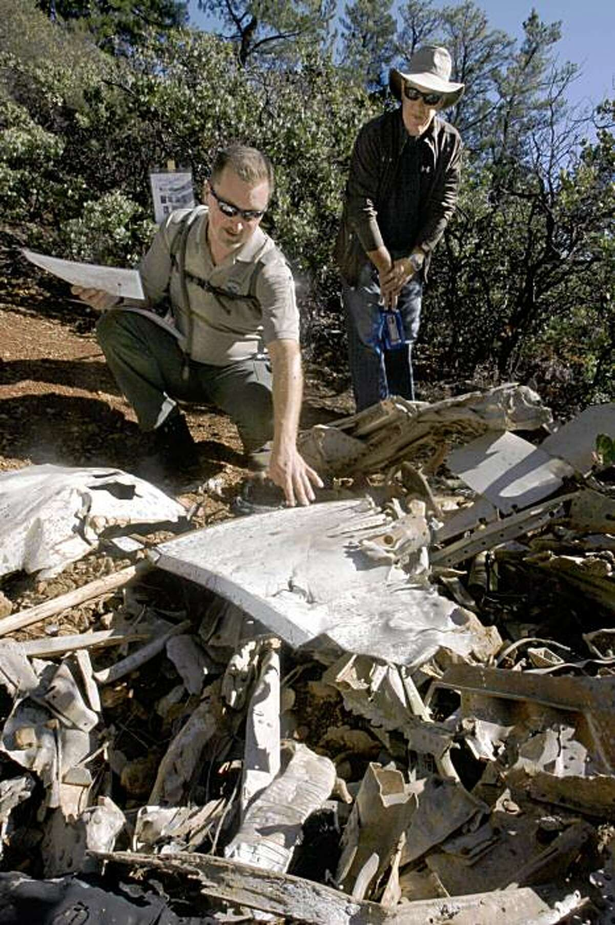 Ranger Matt Cerkel (left) shows pilots of the Gnoss Field Community Association the site of the 1944 naval plane crash on Mt. Tamalpais as he lifts plane parts in Mill Valley, CA, on Monday, November 23 , 2009. On the last day of November, 1944, a navy patrol bomber martin aircraft crashed into the side of Mt. Tamalpais killing all eight aboard. In back is pilot Kevin Rodondi.