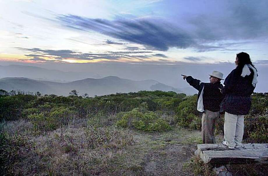 Eric Moberg of Mariposa and friend Charlotte Chan of South San Francisco view the sunset towards the ocean at sunset from the top of the Sweeny Ridge fire trail. SWEENEY RIDGE Photo: Darryl Bush, The Chronicle