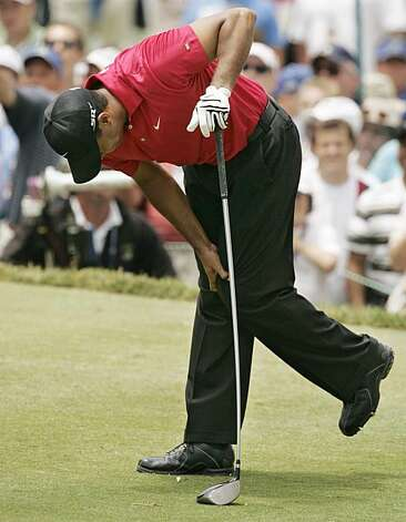 Tiger Woods clutches his left knee after hitting from the second tee during the fourth round of the U.S. Open golf championship at Torrey Pines in San Diego June 15, 2008.     REUTERS/Robert Galbraith (UNITED STATES) Photo: Robert Galbraith, REUTERS