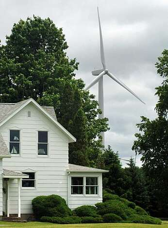 FILE - In this June 9, 2009 file photo, a home is dwarfed by a wind turbine approximately 1,500 feet from his property near Ubly, Mich. A comprehensive report funded by the Department of Energy found that wind farms have no measurable effect on nearby property values. It is unlikely that the report, just the latest to reach the same conclusion, will cool the debate over wind farms that represent progress to some, and aggravation for others.(AP Photo/Bay City Times, Michael Randolph, file) Photo: Michael Randolph, AP