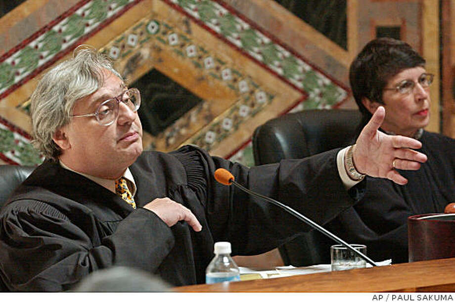 ** FILE** Judge Alex Kozinski, of the 9th U.S. Circuit Court of Appeals, gestures as Chief Judge Mary Schroeder looks on, in this Sept. 22, 2003, file photo in San Francisco. Kozinski, who is currently overseeing a trial in which Los Angeles businessman Ira Isaacs is accused of breaking U.S. obscenity laws, posted sexually explicit photos and videos on his own web site that he maintained is now blocked to the public, the Los Angeles Times reported Wednesday June, 11, 2008, on its Web site. (AP Photo/Paul Sakuma,pool) Photo: PAUL SAKUMA, AP