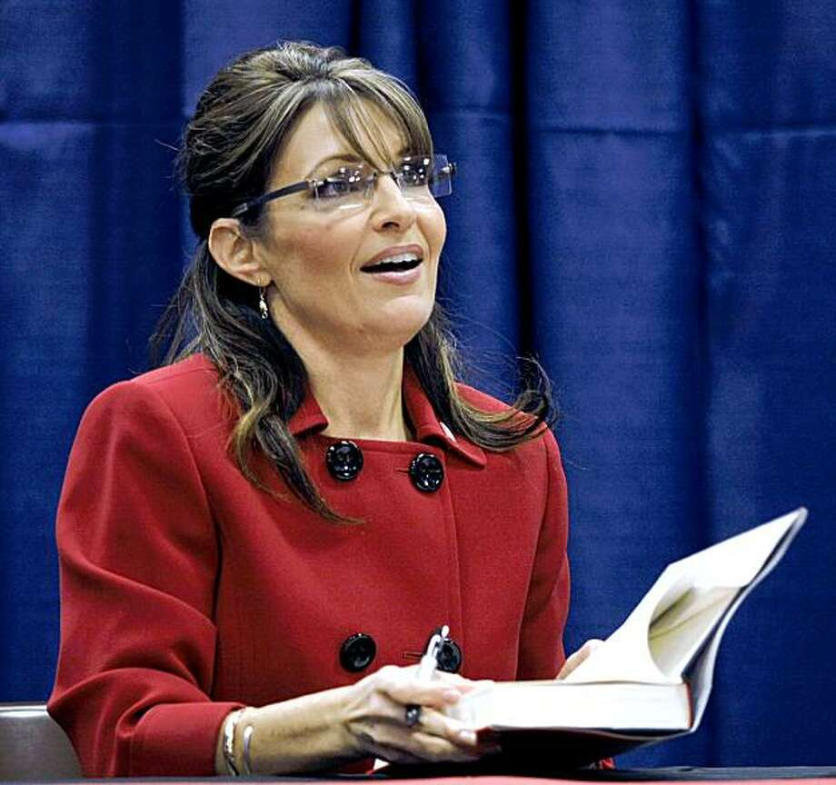 "GRAND RAPIDS, MI -  NOVEMBER 18:  Former Republican vice presidential candidate and Alaska Governor Sarah Palin signs her new book, ""Going Rogue"" for a customer at a Barnes & Noble bookstore November 18, 2009 in Grand Rapids, Michigan. Palin chose Grand Rapids as the first stop of her book signing tour. (Photo by Bill Pugliano/Getty Images) Photo: Bill Pugliano, Getty Images"