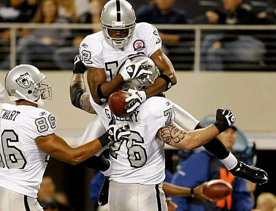 Oakland Raiders tight end Tony Stewart, left, and offensive tackle Robert Gallery (76) celebrate with wide receiver Darrius Heyward-Bey, top, following his touchdown-reception in the second half of an NFL football game against the Dallas Cowboys, Thursday, Nov. 26, 2009, in Arlington, Texas. (AP Photo/Mike Stone) Photo: Mike Stone, AP