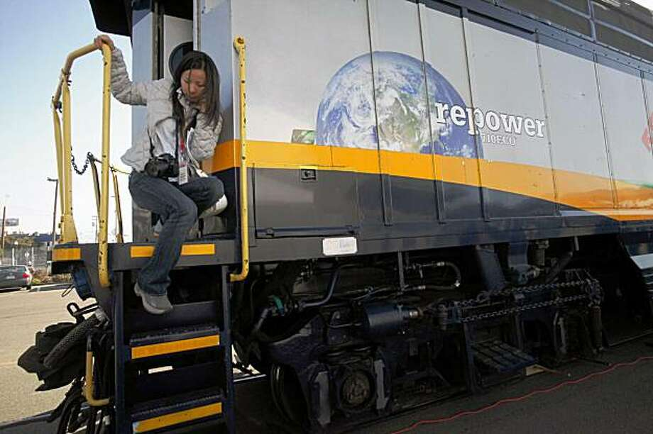 Quiping Han climbs down the back of Amtrak locomotive # 2015, touted as the cleanest diesel passenger train in California, on Tuesday Nov. 17, 2009 in Oakland, Calif. The low emitting train is scheduled to hit the rails between Oakland and Sacramento sometime next week. Photo: Mike Kepka, The Chronicle