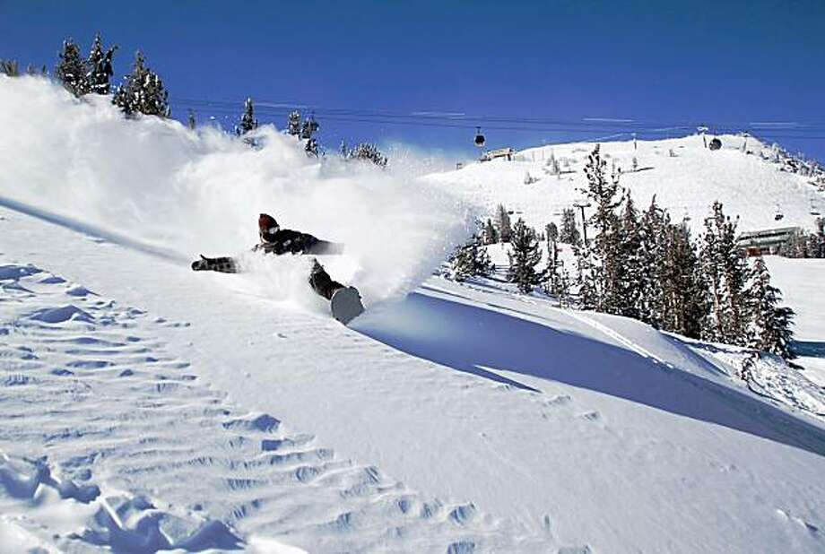 A snowboarder slashes through the powder near McCoy Station on Mammoth Mountain. Photo: Peatross/MMSA