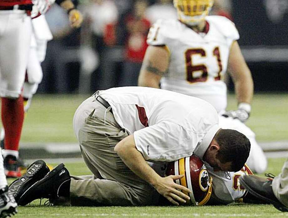 FILE - In this Nov. 8, 2009 file photo, a member of the Washington Redskins training staff, top, attends to running back Clinton Portis after he received a concussion in the first quarter of an NFL football game against the Atlanta Falcons in Atlanta. Thirty of 160 NFL players surveyed by The Associated Press from Nov. 2-15 said they have hidden the symptoms or effects of a concussion so they could continue to play. Portis was not surveyed by the AP. (AP Photo/John Amis, File) Photo: John Amis, AP