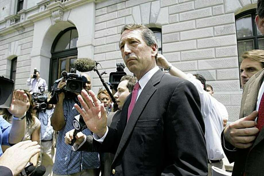 South Carolina Gov. Mark Sanford tries to keep the media back as he makes his way to the Statehouse after a cabinet meeting Friday, June 26, 2009, in Columbia, S.C.  (AP Photo/Mary Ann Chastain) Photo: Mary Ann Chastain, AP