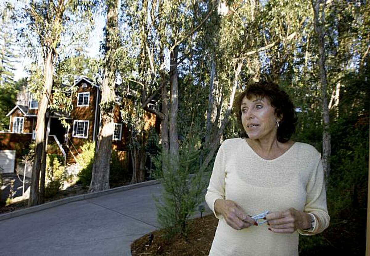 Anne Wolff stands on the driveway of her home in Larkspur, Calif., on Thursday, Nov. 12, 2009. Wolff is in the middle of a dispute with two of her neighbors over a grove of eucalyptus trees on Wolff's property. A Marin County judge has ordered Wolff to cut down over 25 of the trees that have been determined to be hazardous to next door neighbors.