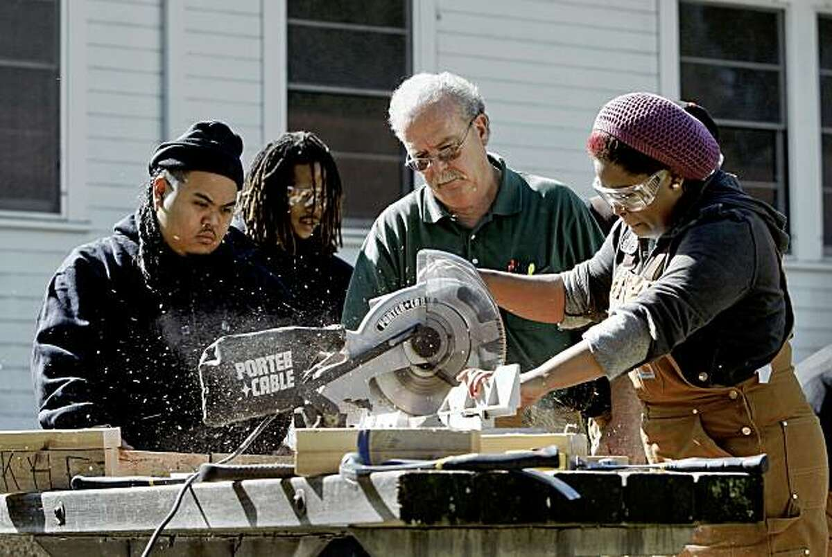 Under the watchful eye of Skills Instructor, Jeff McGallian, (right center) and fellow students, Julius Viclay, (left) and Antoine Hunter, (left center), Deanna Kelly, works the miter saw during a basic carpentry class at John Muir Charter School which works with at-risk youth providing educational and vocational programs, on Treasure Island in San Francisco, Calif. on Thursday October 22, 2009.