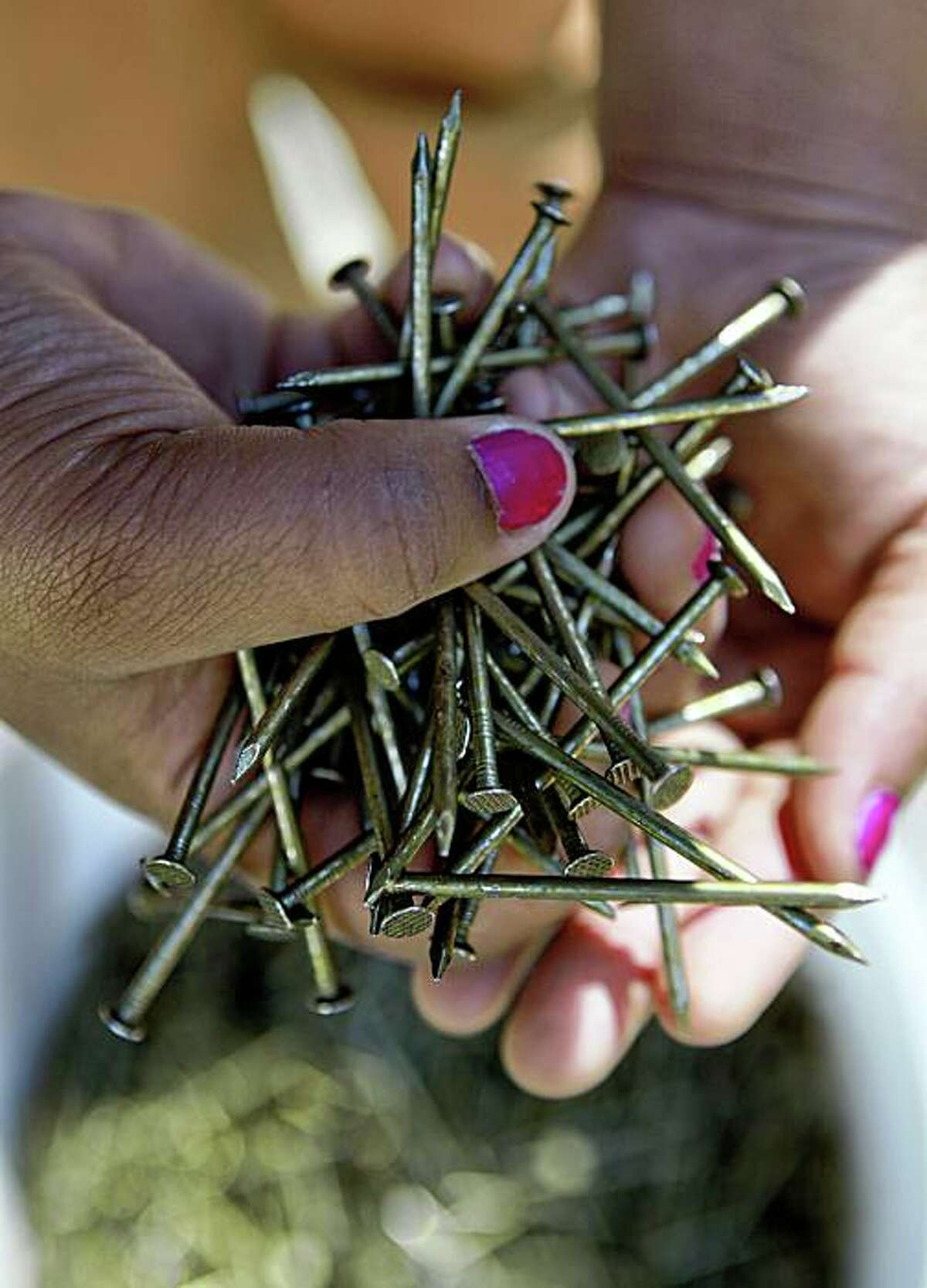 Deanna Kelly, grabs a handful of nails during during a basic carpentry class at John Muir Charter School which works with at-risk youth providing educational and vocational programs, on Treasure Island in San Francisco, Calif. on Thursday October 22, 2009.