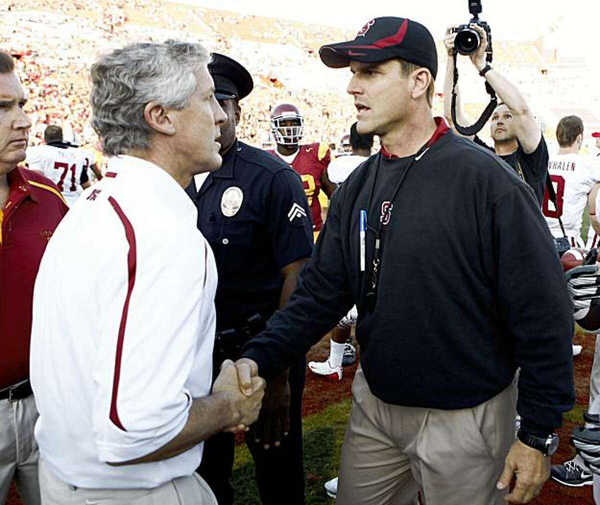 Southern California head coach Pete Carroll, left, and Stanford head coach Jim Harbaugh greet each other after a NCAA college football game in Los Angeles on Saturday, Nov. 14, 2009. Stanford won 55-21. (AP Photo/Matt Sayles)