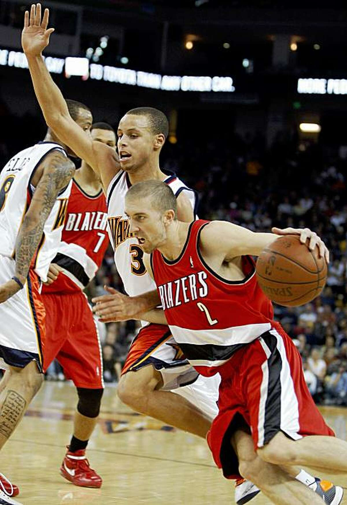 Portland Trail blazers' Steve Blake, right, drives the ball past Golden State Warriors' Stephen Curry during the first half of an NBA basketball game Friday, Nov. 20, 2009, in Oakland, Calif. (AP Photo/Ben Margot)
