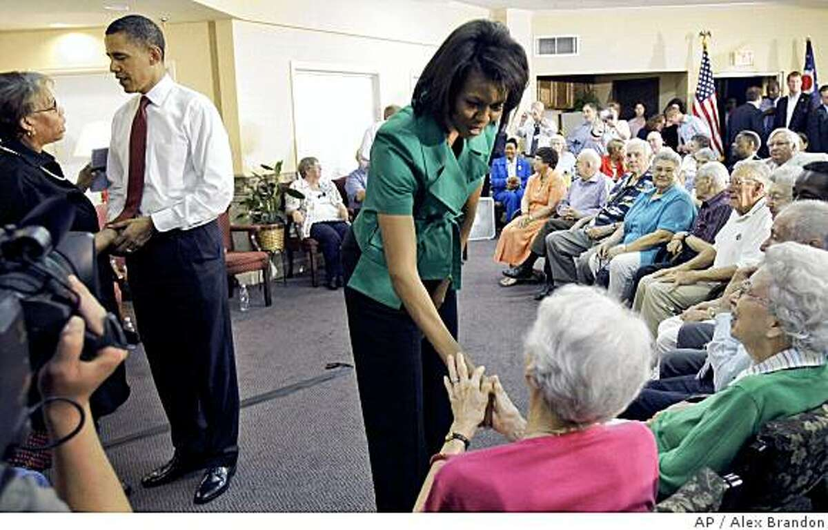 Democratic presidential candidate Sen. Barack Obama D-Ill., left, and wife Michelle Obama, right, shakes hands at the Oakleaf Village retirement community in Columbus, Ohio, Friday, June 13, 2008.(AP Photo/Alex Brandon)