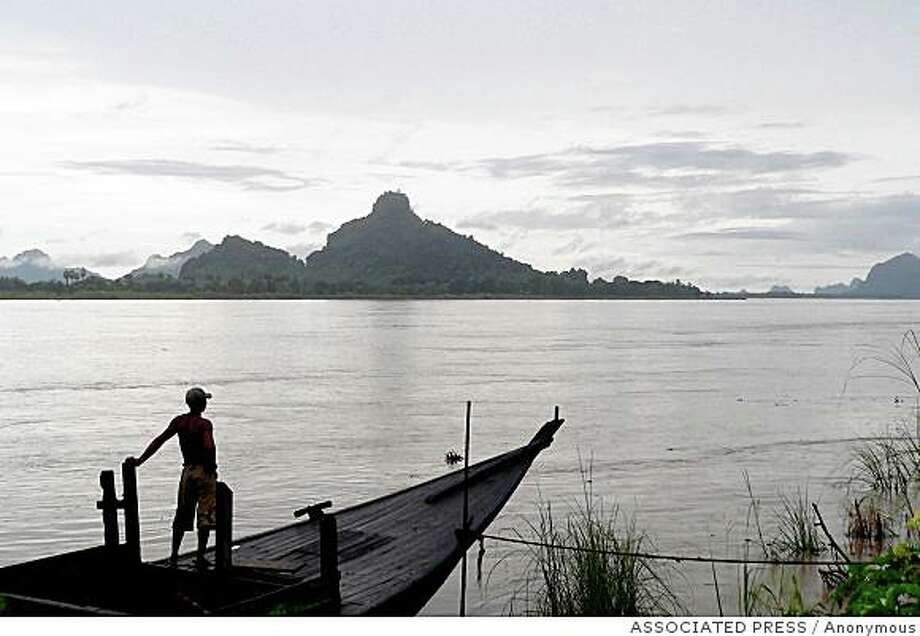 ** ADVANCE FOR WEEKEND EDITIONS, MAY 27-29 **  In this photo released by Southeast Asia Rivers Network, a Karen man looks out from his boat on the bank of the Salween river in Myanmar in March 2006. Rising in Tibet, the 2,800-kilometer-long (1,740-mile) Salween now runs free through a stunningly beautiful, remote and ecologically rich region inhabited mostly by ethnic minority groups. But China's booming economy, projected energy needs in Thailand and current deficits in impoverished Myanmar are driving economic planners into hitherto undisturbed areas in quest of hydro-electric power dam. (AP Photo/Southeast Asia Rivers Network, HO) Photo: Anonymous, ASSOCIATED PRESS