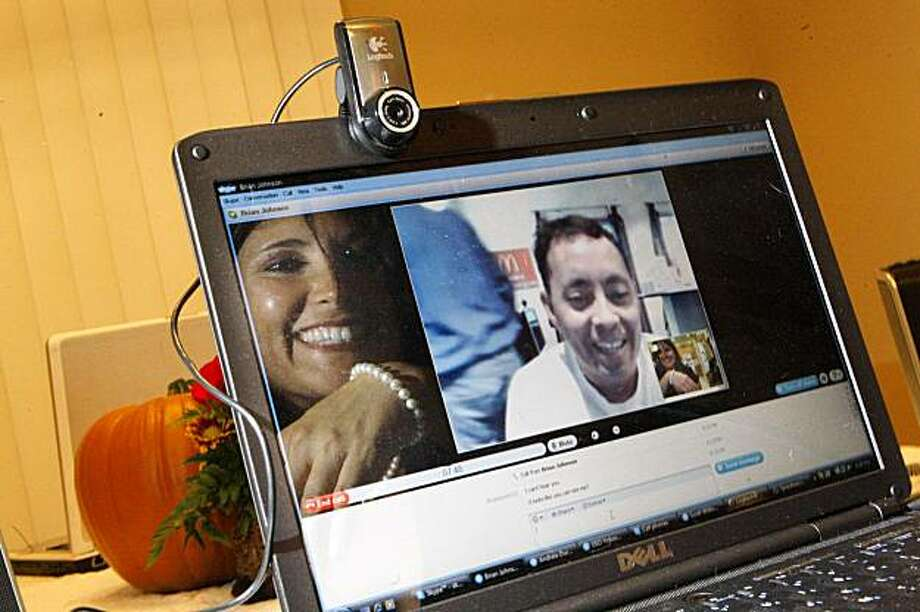 Kelly Harris (right) of San Jose, who is reflected in her computer screen, holds up her wrist to show her brother, Brian Johnson (center)  the pearls that he gave her in 2005, as she talks to her brother, who is stationed in Japan, through a video phone call via Skype for Thanksgiving from San Jose, Calif. on Wednesday November 25, 2009. The pearls were given to her by her brother in 2005, shortly after she had been diagnosed with leukemia and after she had been given her last rites. Photo: Lea Suzuki, The Chronicle