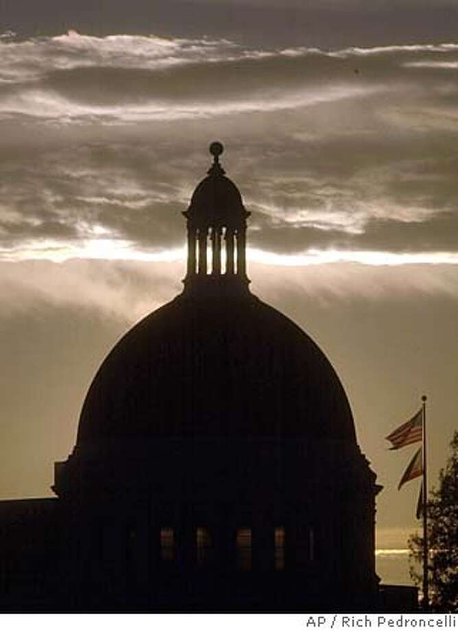 The dome of the California Capitol buiding is seen against the setting sun Wednesday, Jan. 9, 2002. (AP Photo/Rich Pedroncelli) Photo: RICH PEDRONCELLI