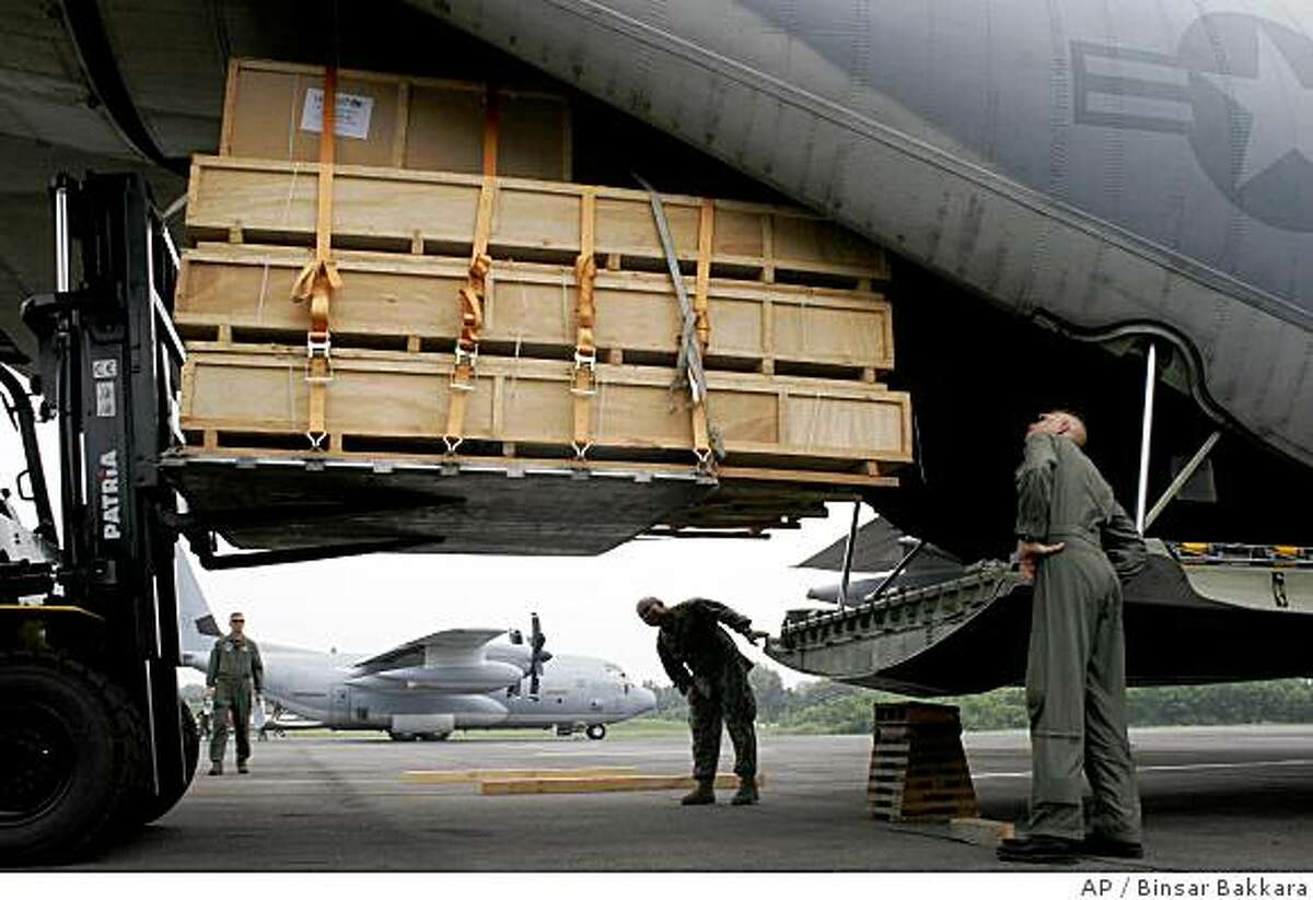 U.S. soldiers from Marine Aircraft Group 36 load a cargo of UNICEF aid onto a U.S. cargo plane for cyclone victims in Myanmar, Friday, June 6, 2008, in Medan, North Sumatra, Indonesia. The plane was due to fly the aid first to Thailand from where it would be flown into Yangon. (AP Photo/Binsar Bakkara)