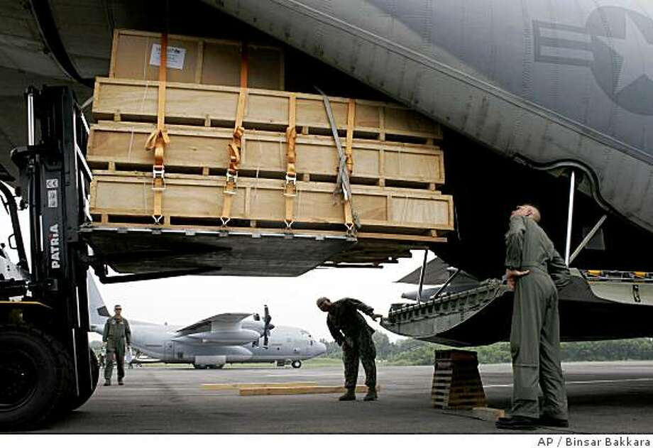 U.S. soldiers from Marine Aircraft Group 36 load a cargo of UNICEF aid onto a U.S. cargo plane for cyclone victims in Myanmar, Friday, June 6, 2008, in Medan, North Sumatra, Indonesia.  The plane was due to fly the aid first to Thailand from where it would be flown into Yangon.  (AP Photo/Binsar Bakkara) Photo: Binsar Bakkara, AP