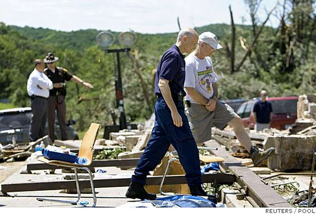 Homeland Security Secretary Michael Chertoff tours the tornado damage with Dave Jacobs, who said he was in charge of cooking at the camp, at the Little Sioux Scout Ranch near Little Sioux, Iowa June 12, 2008. Tornadoes killed four people at the Boy Scout camp in Iowa and two others in Kansas as more than 30 twisters ripped through the U.S. Midwest, rescue officials said on Thursday. REUTERS/Omaha World-Herald/Matt Miller/Pool (UNITED STATES)
