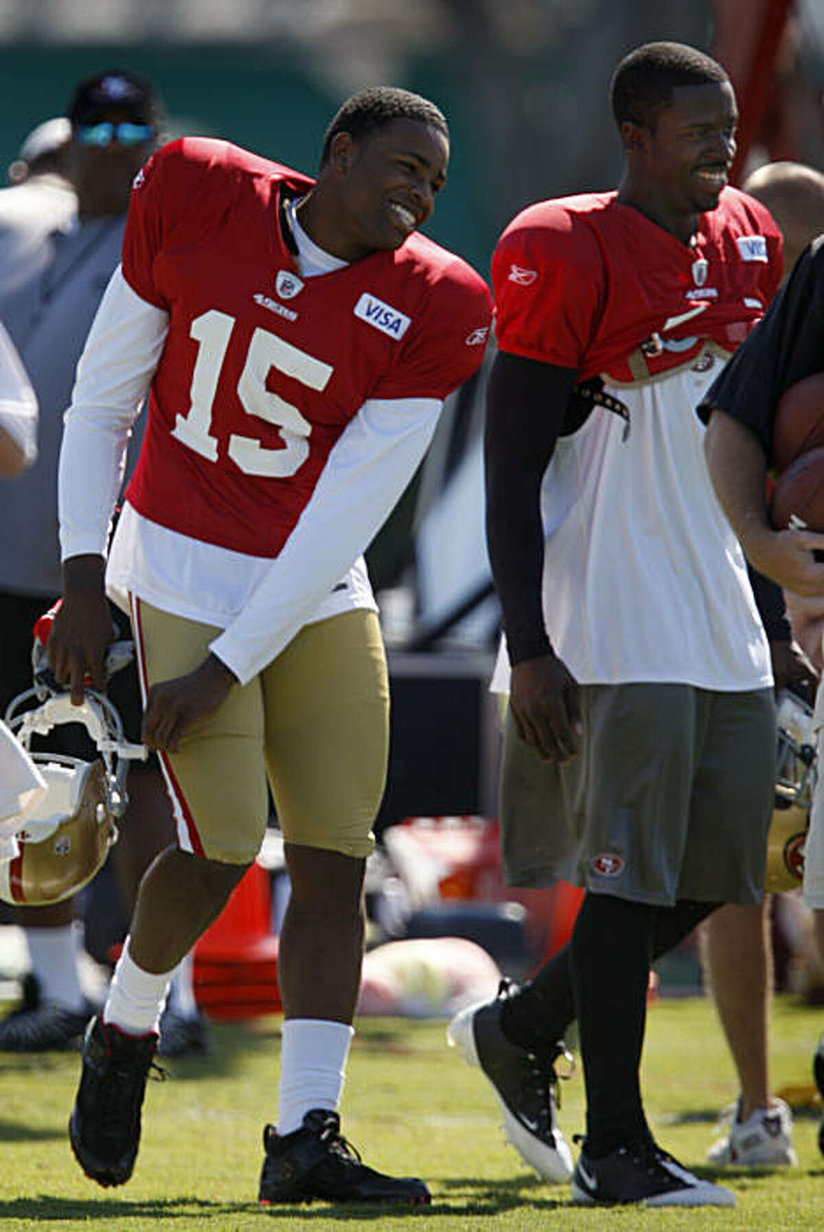 Newly-signed San Francisco 49ers wide receiver Michael Crabtree (15) laughs with teammate Josh Morgan at Crabtree's first practice at the team's headquarters in Santa Clara.