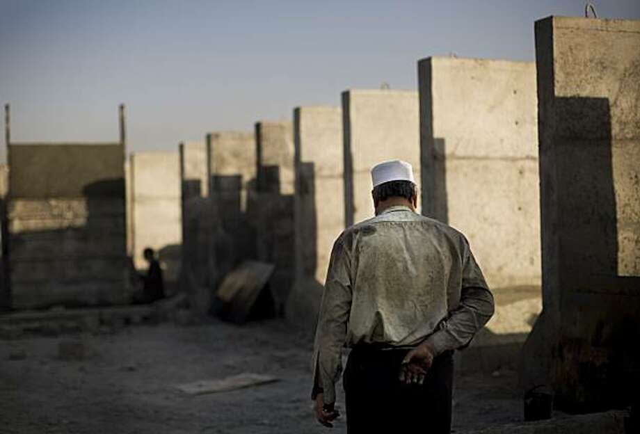An Afghan worker passes by concrete blast walls in the outskirts of Kabul, Afghanistan, Tuesday, Nov. 17, 2009. With security worsening and thousands of international troops being additionally expected by next year, business is going up for concrete blast walls. (AP Photo/Anja Niedringhaus) Photo: Anja Niedringhaus, AP