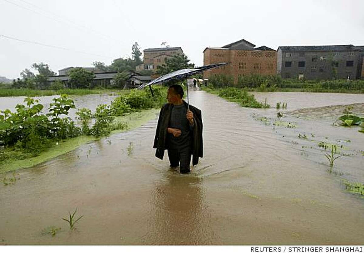 Wu Qinnan, 63, walks along a flooded road near his village on the outskirts of the Shapingba District of Chongqing municipality June 15, 2008. At least 55 people have been killed over the past 10 days in torrential rain and flooding across south China, and more gales and storms were expected in the coming days, the government said on Sunday. REUTERS/Stringer (CHINA). CHINA OUT. NO COMMERCIAL OR EDITORIAL SALES IN CHINA.