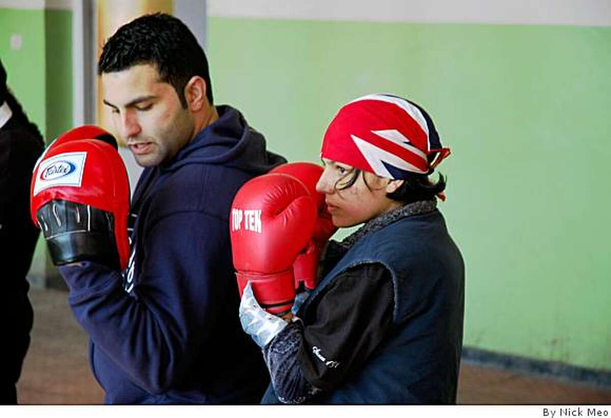 Concord native Tareq Shawl Azim teaches 15-year-old Shabnam Rahimi how to box at the National Stadium in Kabul.