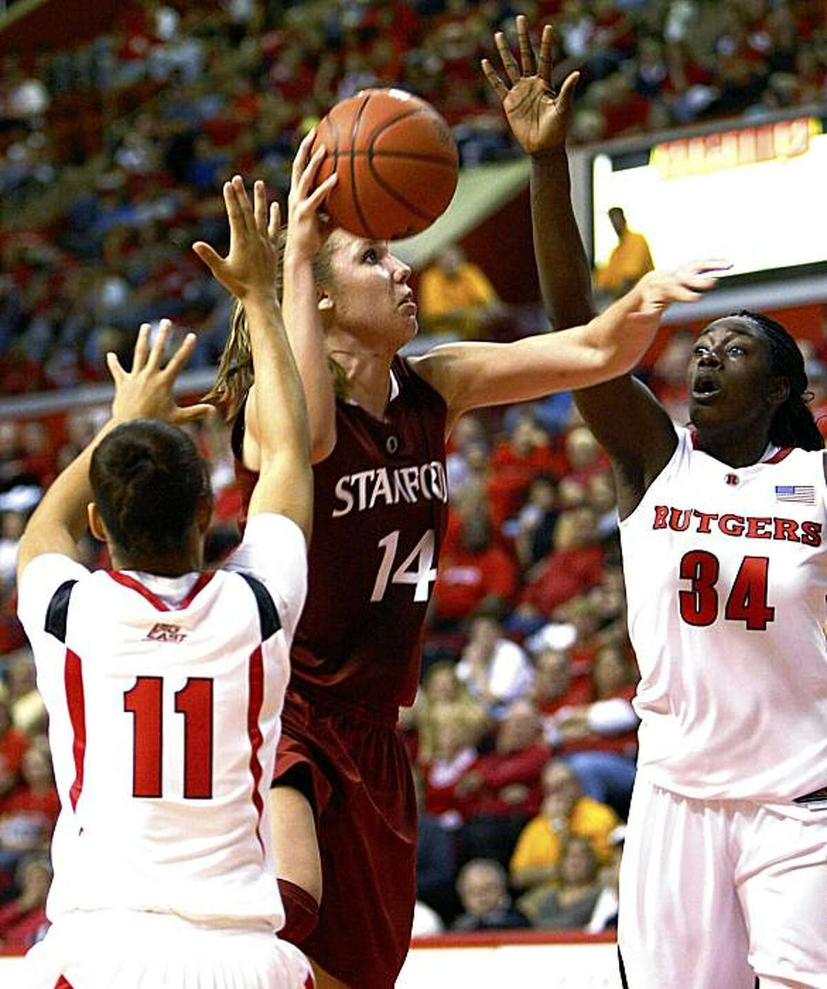 Stanford's Kayla Pederson (14) shoots between Rutgers' Nikki Speed (11) and Chelsey Lee (34) during the second half of an NCAA women's college basketball game in Piscataway, N.J., on Sunday, Nov. 15, 2009. Stanford won 81-66. (AP Photo/Tim Larsen)