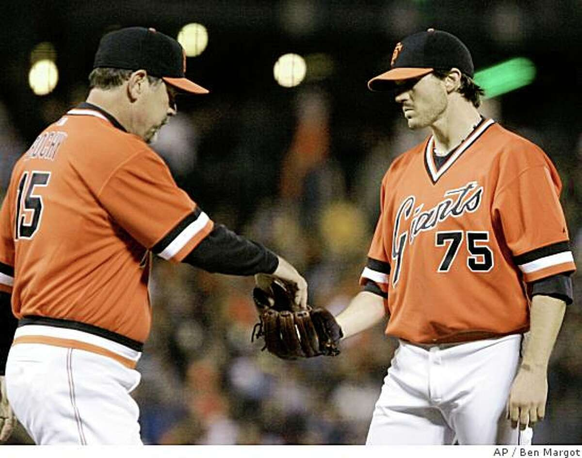 San Francisco Giants manager Bruce Bochy, left, takes the ball from starting pitcher Barry Zito in the sixth inning of a baseball game against the Oakland Athletics on Friday, June 13, 2008, in San Francisco. (AP Photo/Ben Margot)