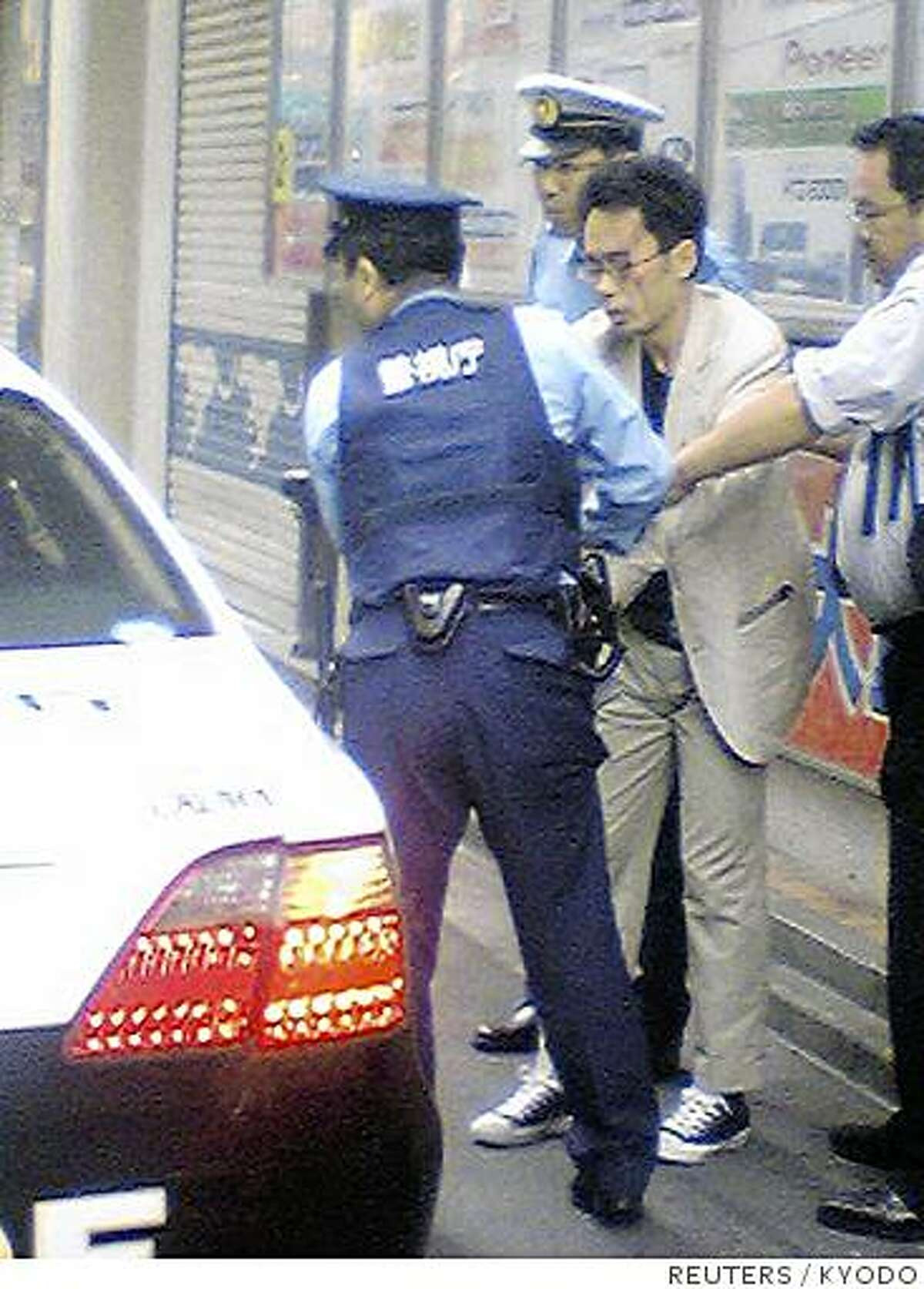 Tomohiro Kato (C), who killed seven people and wounding a dozen others, is detained by police officers at Tokyo's Akihabara district June 8, 2008 in this photo taken by an anonymous pedestrian. Kato, who said he was tired of life went on a stabbing rampage on Sunday in a crowded Tokyo shopping street, knifing passers-by in Akihabara, known of its discount electronics and maid cafes. Picture taken June 8, 2008. QUALITY FROM SOURCE REUTERS/Kyodo (JAPAN). JAPAN OUT. NO COMMERCIAL OR EDITORIAL SALES IN JAPAN.