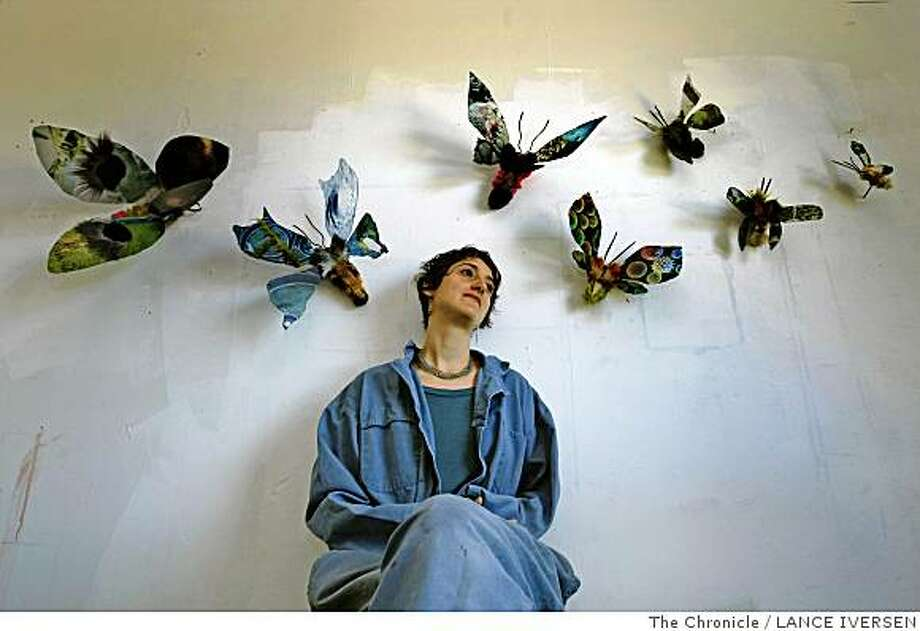 Ana Labastida an artists from Mexico poses for a portrait with her Moths that hang on displays in her new Emeryville studio. Artists from Mexico have been finding a home and some inspiration in the San Francisco Bay area at least as far back as Diego Rivera and Frida Kahlo�s residency here in 1930. Nowadays a crop of young Mexican artists are creating new work here in the Bay Area, bringing a fresh lens to issues like border walls and the fragility of urban landscapes. Photographed in Emeryville Calif, May 1, 2008 Photo By Lance Iversen / San Francisco Chronicle Photo: LANCE IVERSEN, The Chronicle
