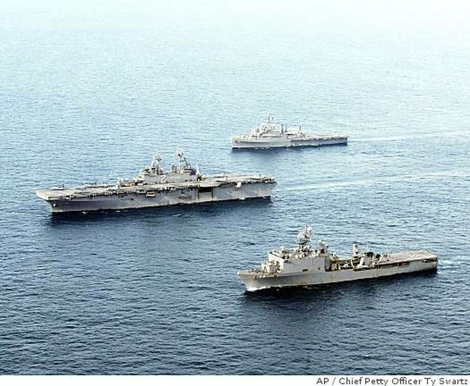 ** FILE ** In this May 23, 2008 file photo released by U.S.Navy, the USS Essex , center, and the Essex Amphibious Ready Group steam in formation, in the Andaman Sea.  The Essex Amphibious Group is standing by in international waters off the coast of Myanmar in support of Joint Task Force Caring Response, a humanitarian assistance operation developed in the wake of Cyclone Nargis.  The U.S. military ordered the navy ships loaded with relief aid off Myanmar's coast to leave the area Thursday after the country's xenophobic junta refused to give them permission to help survivors of last month's devastating cyclone.  (AP Photo/U.S. Navy, Chief Petty Office Ty Swartz, HO, FILE) Photo: Chief Petty Officer Ty Swartz, AP