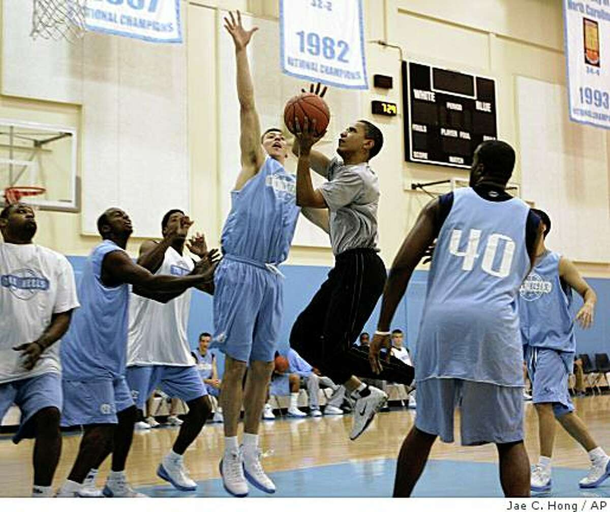 Democratic presidential hopeful Sen. Barack Obama, D-Ill., center right, drives to the basket against the University of North Carolina's Tyler Hansbrough during a basketball game in Chapel Hill, N.C., Tuesday, April 29, 2008. (AP Photo/Jae C. Hong)
