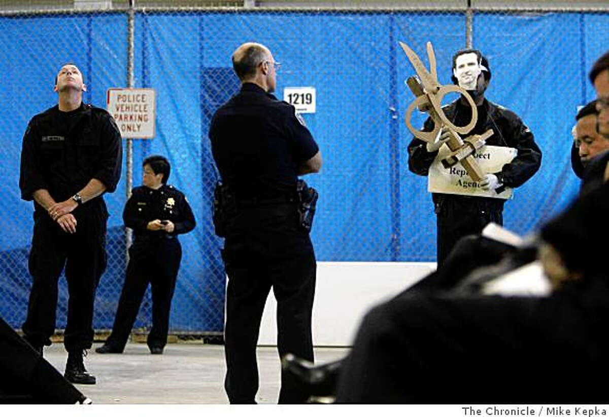 A protest who refused to reveal his identity carefully watched by members of police force as San Francisco Mayor, Gavin Newsom addresses his new budget plan in the San Francisco Police Department Tactical Operations center located in Hunter's Point Shipyard on Monday, June 1, 2008, in San Francisco,Calif.