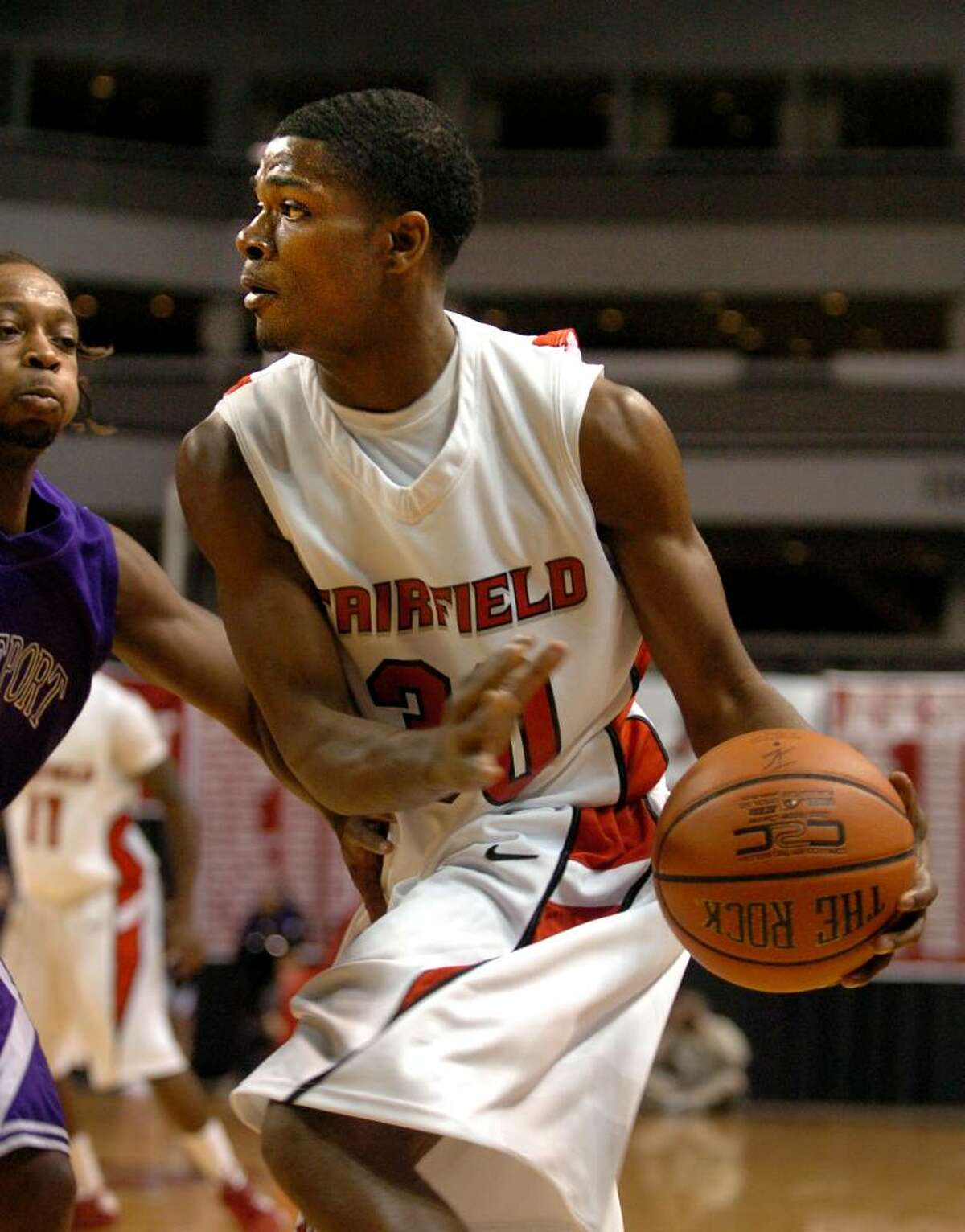 Fairfield University's Shimeek Johnson looks for a hole to pass as Bridgeport University's Steve Martin defends, during men's hoops at the Arena at Harbor Yard in Bridgeport, Conn. on Thursday Nov. 05, 2009.