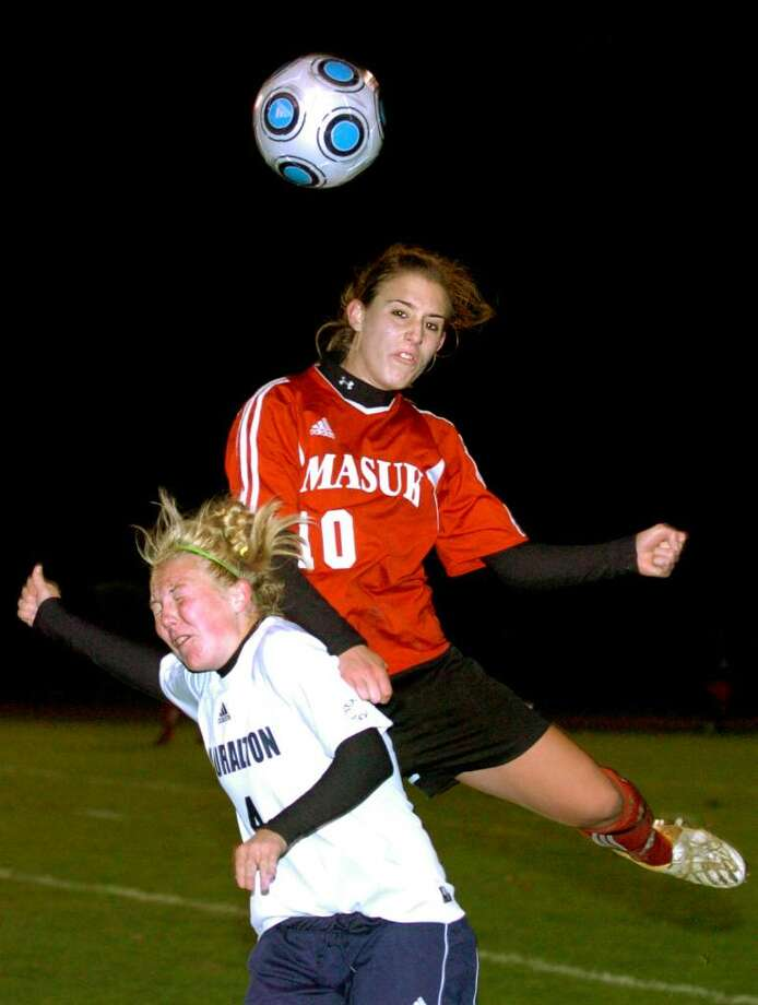 Masuk's Marissa Maiolo knocks into Lauralton Hall's Allison Miles as she heads the ball in the second half of Thursday night's South West Conference Girls Soccer Championship at Joel Barlow High School. Photo: Autumn Driscoll / Connecticut Post