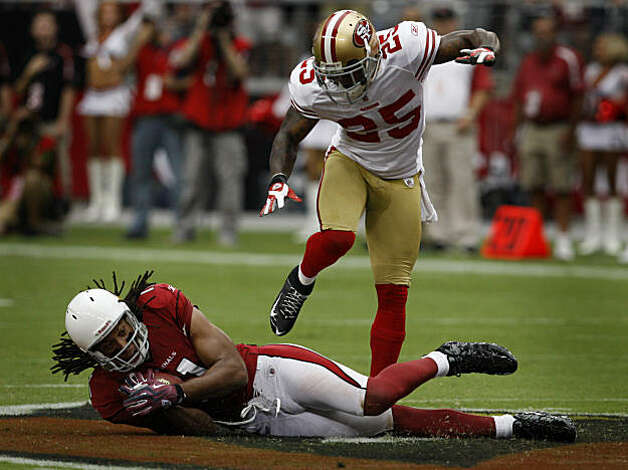 Cornerback Tarell Brown (25) makes sure receiver Larry Fitzgerald doesn't get up after a reception in the first quarter of the San Francisco 49ers vs. Arizona Cardinals NFL game in Glendale, Ariz., on Sunday, Sept. 13, 2009. Photo: Paul Chinn, The Chronicle